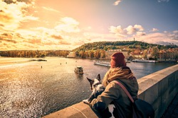 Young women tourist with a puppy dog and a backpack looking at the tourist boat and swans sailing on Vltava river from the Charles Bridge (Karluv Most) in Prague, Czech Republic.