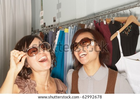 Young women trying on sunglasses
