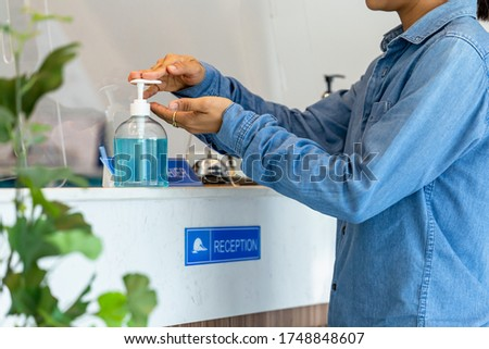 Young women washing hands with alcohol gel at modern luxury hotel reception counter desk with bell,Pen and wood calendar.hand sanitizer gel to wash hands for virus protection ( Covid-19)