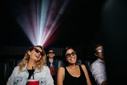 Young women watching 3d movie in cinema. People in theater with 3d glasses.