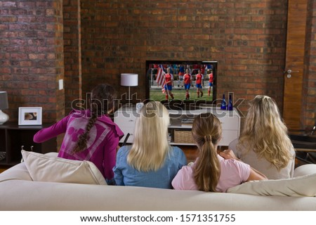 Young women watching women's soccer game on TV