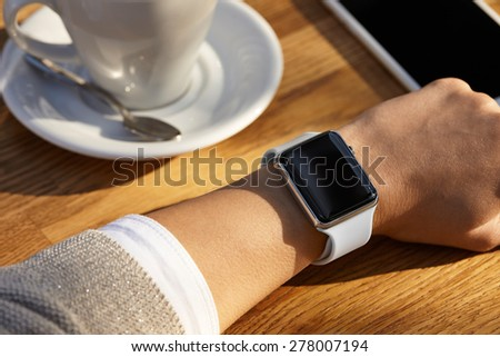 Young women wears smart watch and drinks coffee