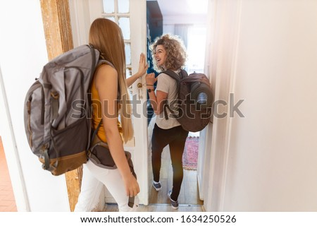Young women with backpacks arriving to a youth hostel  Сток-фото ©