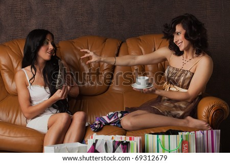 Young women with money and shopping bags sit on leather sofa at home. Sale.