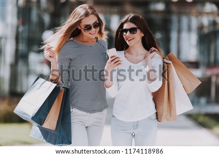 Young Women with Shopping Bags Walking City Street. Sale, Consumerism and People Concept. Shopping and Tourism Concept. Girls Bags Walking Down the Street on Sunny Day after Good Shopping.