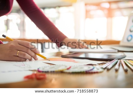 young women working as fashion designer drawing sketches for clothes in atelier paper at workplace studio #718558873