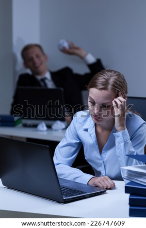 Young worker bullying his young attractive work colleague