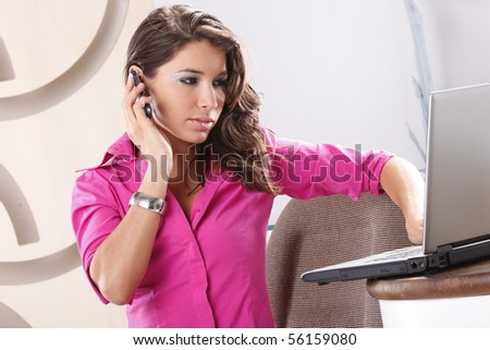 Young worker calling while browsing her laptop
