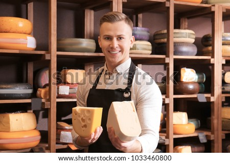 Young worker holding different cheeses in shop