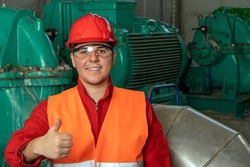 Young Worker in Red Coveralls and Hardhat Standing in Industrial Interior and Giving Thumbs Up. Portrait of Smiling Young Worker in District Heating Power Plant.