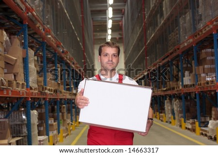 young worker in uniform carrying box in warehouse