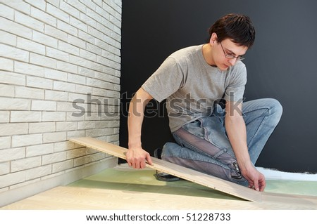 Young worker laying a floor with laminated flooring boards