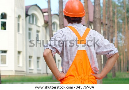 Young worker looking at the building. Rear view