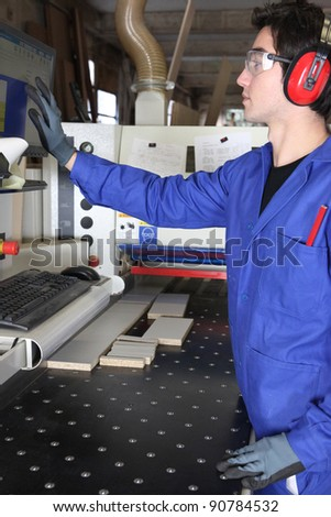Young worker operating factory machine