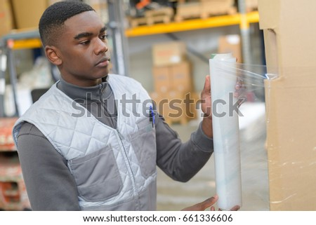 Young worker shrink wrapping pallet
