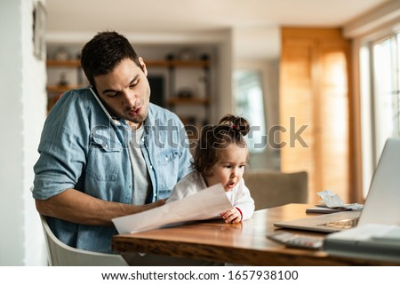 Young working father babysitting his small daughter and making a phone call at home.