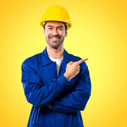 Young workman with helmet pointing to the side with a finger to present a product or an idea while looking forward smiling on yellow background