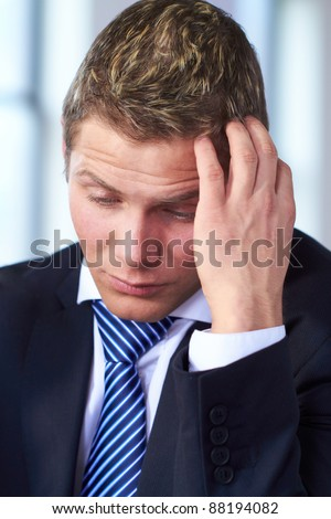 Young worried and stressed businessman scratch his head, very sad face expression