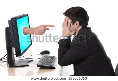 young worried business man deppressed in stress with computer hand with accusing finger pointing him in failure, crisis and financial ruin concept and social network media cybermobbing and bullying