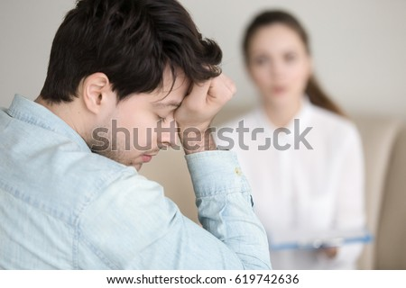 Young worried guy touching his forehead, having a headache or migraine, overworked businessman feeling tired, stressed and exhausted, female doctor, nurse or colleague standing in the background