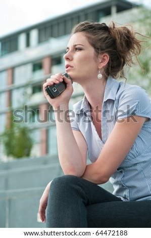 Young worried woman with unhappy expression holding mobile phone - outdoors in urban setting
