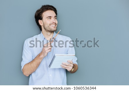 Young writer. Happy positive nice man holding his notebook and smiling while feeling inspiration