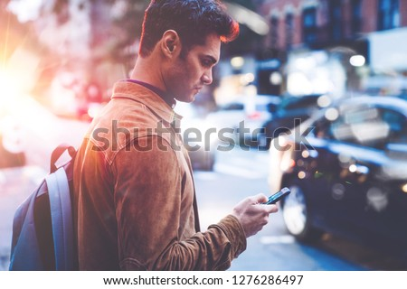 Young 30 years old brunette male ordering taxi via cab application on smartphone while standing on city street at evening. Man texting message in chat on mobile phone walking outdoors. 4G internet