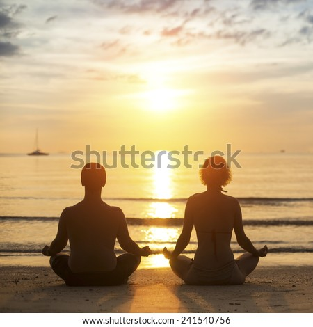 Young yoga couple is meditating in the Lotus position on the sea beach during sunset.