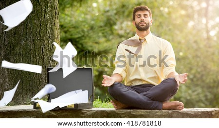 Young yoga position businessman relaxing in nature outdoor