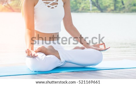 young yoga -relax in the park , with sun light.