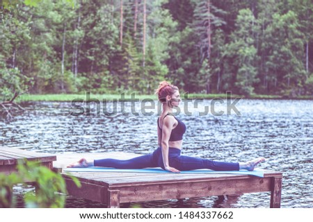 Young yogi  girl  practicing yoga, stretching in Monkey God exercise, Splits, Hanumanasana pose on the lake. The concept of appeasement,  healthy lifestyle.