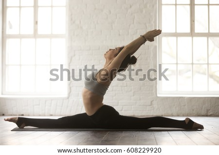 Young yogi woman practicing yoga concept, stretching in Monkey God exercise, Splits, Hanumanasana pose, working out, wearing black sportswear, full length, white loft studio background, side view