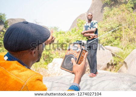 young young black man holding a radio giving thumbs up to a friend who's dancing  #1274027104