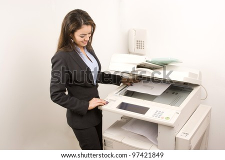 Young young businesswoman making copies on the photocopy machine at the office