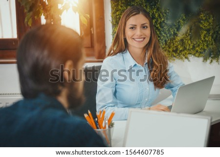 Young young cute woman and handsome serious pensive businessman working on laptop at the office.