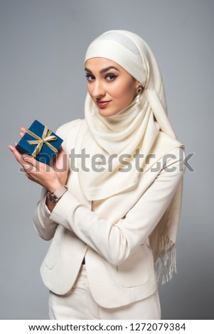 young young muslim woman holding present and smiling at camera isolated on grey