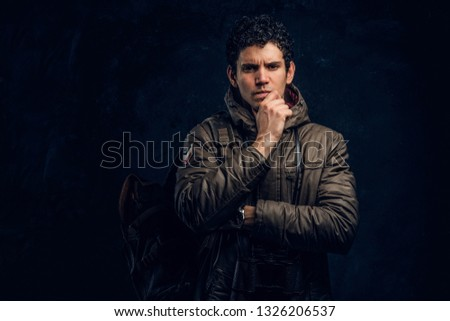Young young traveller in a hiking outfit with binoculars stands with a thoughtful look in the studio against a dark wall