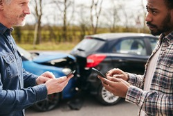 Younger and older drivers at side of the road exchanging car insurance details after traffic accident using mobile phones