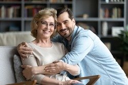 Younger and older generation relatives people portrait, love, care, connection, family bonds concept. Grown up adult son hugs elderly mother while she resting seated on cozy comfort armchair indoors