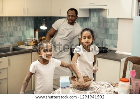 Younger and older. Younger and older sisters feeling truly happy and joyful while cooking together
