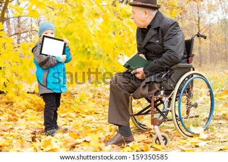 Youngster showing a disabled man a tablet-pc screen as the elderly gentleman sits in his wheelchair in a colourful yellow autumn park enjoying reading his book