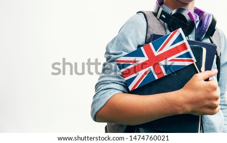 Youngster with school stuff demonstrating United Kingdom flag closeup