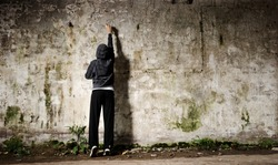 Youngster with spray paint and an empty wall for graffiti