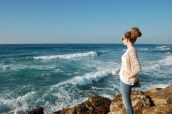 youngyoung curly-haired girl, looking into the distance of the sea, in jeans, glasses, surf stones on vacation by the sea, tourism, blue sea curly-haired girl, looking into the distance of the sea,