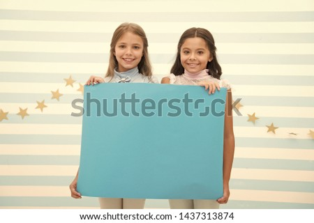 Your advertisement in good hands. Girls kids hold advertisement poster copy space. Children hold advertising banner. Happy children with blank paper for advertisement. Advertisement concept. #1437313874