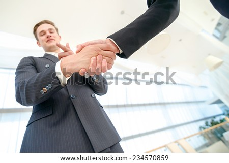 Your choice in business. Two Confident businessman shake hands with each other in the business office until one businessman points his finger at the camera