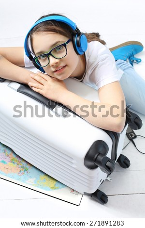 Your journey of dreams.\ Girl in blue headphones packed suitcase with things for a holiday trip