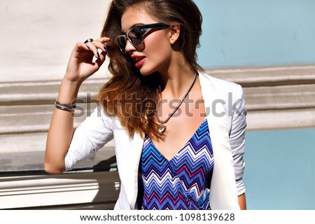 Your pretty elegant business woman posing on the street, fluffy hairs sunglasses and jacket, glamour style and bright colors. Jewelry and accessories.