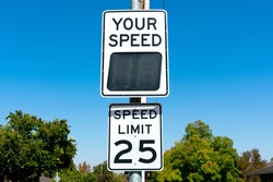 Your Speed, a radar speed sign that displays vehicle speed as motorists approach. 25 mph speed limit sign in residential neighborhood.