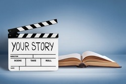 Your story .Text title on film slate and old book on blue background.